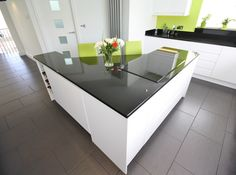 Second Nature - Remo white gloss units, black granite worktop and a splash of lime green!