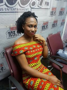 Beautiful woman in Hit FM Studios in a colorful African Dress style.