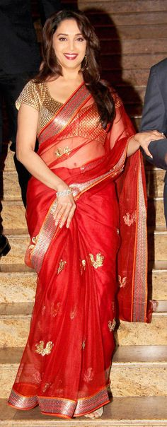 Madhuri Dixit looked red hot (literally!) in a gold and red SVA sari at the launch of Dilip Kumar's autobography.