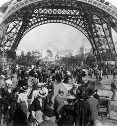 France. Visitors to the World Exposition walking under the Eiffel Tower, with a view of the Chateau d'Eau in the background, Paris, 1900 // Photo by Hulton Archive/Getty Images