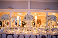 Brea McDonald Photography and Soiree Floral of Nantucket, Elevated centerpieces of white flowers that include roses, hydrangeas and dendrobr...