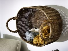 Basket yarn storage - I would not have thought to hang the basket on the wall like this.