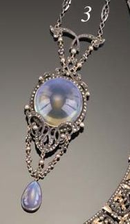 Sibyl Dunlop. An Arts and Crafts moonstone, marcasite and half-pearl pendant centred on a circular cabochon moonstone with silver scroll mounts and garland chains to a drop-cut moonstone drop, on a chain, apparently unmarked, in a case, the lining stamped Sibyl Dunlop Ltd., 69 Kensington Church St., London, W.8. Sold by Christies.