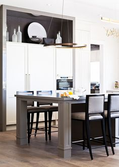 In the kitchen seating area, Metcalfe upholstered Kravet barstools in an indoor/outdoor fabric for increased practicality. A bronze halo light by Le Deun Luminaires complements the linear design elements of the space.