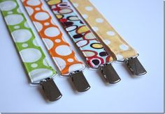 """To make a pacifier clip (I have an aversion to the word Binky… by the way), you need:  Assorted Fabric, cut 10 1/2"""" x 4""""  Coordinating thread  1"""" Suspender Clips (you can find them in the notions section at your fabric store, or online)  Various ribbon, 3/8"""" – 1/2"""" wide  Here are a few fabrics I pulled out from my stash.  The pink will be for a gift, eventually!  010  To begin, iron a 1/4"""" hem on the 4"""" sides of your fabric rectangles.   011  Next, iron your fabric in half, hot-dog ..."""