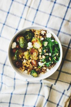 Quinoa bowl with roasted brussels sprouts, wilted greens, feta, pine nuts