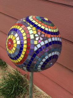 Mosaic stained glass garden orb constructed on a bowling ball base. The pieces for the designs are all hand cut stained glass. The colors used for this ball are lime, yellow, pink, cream, red, blue, turquoise and green. On the bottom one hole has been left open so orb can be mounted on a very sturdy pole or it can be set on a stand. If you live in a climate with frost or freezing, orb should be over wintered inside. Otherwise it is made to enjoy in your garden or on a porch, patio or…