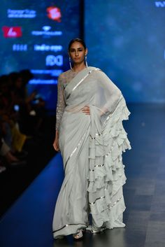 Rabani & Rakha play with textures in this aqua blue sari with a ruffled pallu, complemented by the embroidered blouse. Style it with shoulder grazing earrings and a clutch in a bright colour. Women's Dresses, Indian Dresses, Indian Outfits, Ruffled Dresses, Fashion Dresses, Summer Dresses, India Fashion Week, Fashion Week 2018, Tokyo Fashion