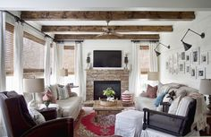 This is how I want our living room. Fire place. planked walls. lights over wall gallery. window treatments. Two chairs. LOVE