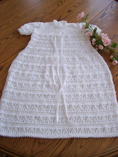 Ready to Ship.  This is a new hand knit Christening Gown and Bonnet Set (Bonnet not shown). It is made from snow white baby yarn and is made to fit 6-12 months in size. It is about 28 inches from shoulder to hem with a nice little picot hem on the bottoms of the skirt. Sure to be a family heirloom to be passed down. Care instructions: Machine wash on delicate for 2 min, then dry on low heat for maximum of 5 min. Remove and lay flat to finish drying. Do not dry clean.