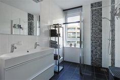 Kleine badkamer met dubbele wastafel en inloopdouche