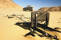 Africa, Libya, Fezzan. Land Rover Defender 110 behind the remains of a during World War Second destroyed Italian military Fiat 634 truck in a valley of the Gebel Sherif mountains southwest of Kufra. Libye