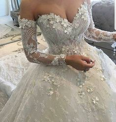 This long sleeve bridal gown has pretty flower embellishments.  The off the shoulder design is flattering to most figures.  We can make ball gown style #weddingdresses like this with any design changes for our #brides.  We also make #replicas of haute couture designer #dresses for brides who love a style but can not afford the original couture cost.  We can work with brides long distance.  Find out how and get pricing when you email us directly from our website.