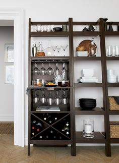 Space-saving, clean-looking Sawyer uses an ingenious leaning, modular design to creatively solve storage solutions throughout the home. Solid mahogany and mahogany veneer media storage extends vertical uprights with a single high shelf. Down below bar features a drop-down work station and gadget drawer for cocktail prep, underlying stemware racks and X-designed storage for wine bottles. Flanking bookcases ladder five deep shelves with thick shelf fronts.