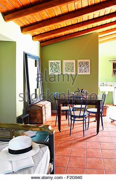 Dining area with terracotta floor tiles and green walls - Stock Photo