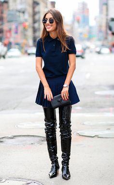 Patricia Manfield com look ousado de polo e saia azul marinho com over the knee de verniz preta