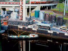 Ein kleines Küstenmotorschiff hat getankt und gerade wieder abgelegt. In zahlreichen Hochbehältern wird neben der Raffinerie Treibstoff unterschiedlicher Art und Qualität vorrätig gehalten.