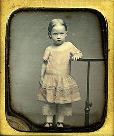 A rather grumpy little girl posing for a portrait in the 1850s.