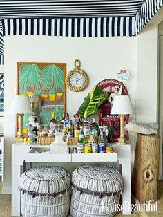 """A console serves as a bar in the sunroom of designer Amanda Lindroth's Bahamas house. """"Every island house needs a fantastic, spilling-over bar,"""" she says. A painting by the prominent Bahamian outsider artist Amos Ferguson serves as a backdrop. Poufs and rope clock from Two's Company."""