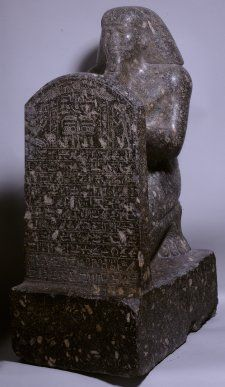 Granodiorite kneeling stelophorous statue of Mentuemhat; stela bears offering-scene above eleven rows of Hieroglyphic text; two columns of Hieroglyphic text on the back-pillar.  LP EA  1643