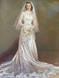 Noiva tradicional dos anos 50, com vestido de cauda longa, gola mais alta e buquê branco.