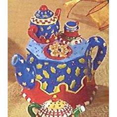 Teapot is mainly blue and red in color. It does have yellow and other multiple colors in it On the top of the teapot is another smaller teapot with a cup and saucer. It also has another plate on the t