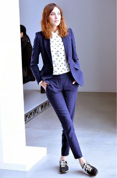 Alexa Chung wears a printed button-down shirt, navy suit, and New Balance sneakers