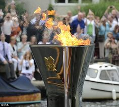 The Olympic Flame burns in the cauldron on the Royal rowbarge Gloriana