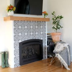A black and white tile fireplace with green rain boots