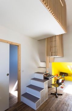 La mezzanine offre une chambre (2 x 2m) aux filles de Gilles de passage le week-end. Le faux plafond enlevé était en charpente, et le bois a servi à bâtir la mezzanine consolidée par des tiges filetées, qui, suspendue aux poutres du plafond, assure la stabilité. Les façades en tasseaux laissent passer le jour. Gilles a conçu l'escalier /bureau menant à la mezzanine. Ce meuble est structuré par une armature en métal, des tasseaux en sapin et par les marches en contreplaqué aménagées de…