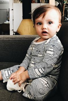 Little cutie lounging on the sofa in adorable baby jumper from Noble Carriage's Winter Water Factory collection. Cozy comfy and so soft, perfect for jammies or for playtime. Hipster style with intricate sailboat illustration, chic monochrome outfit. Made from organic cotton.