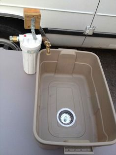 Washtub for camping with a drain out of a plastic storage tub. Insert into a folding table to make a wash and prep station.