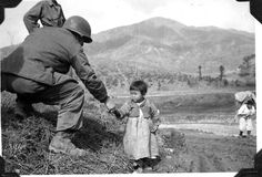 Soldier sharing food with Korean child.