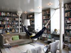 i love the walls filled with books! and that hammock is pretty sweet, too....