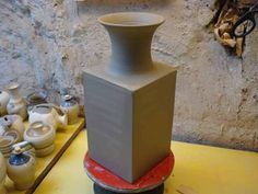 Making / Throwing a square pottery clay vase on the wheel