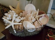Love this display of ocean goodies in a wire basket.