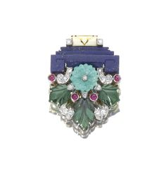 GEM-SET AND DIAMOND CLIP, CARTIER, CIRCA 1930.  Of giardinetto design set with carved lapis lazuli, turquoise, tourmaline and cabochon rubies, highlighted with cream enamel, circular and single-cut diamonds,signed Cartier and numbered.