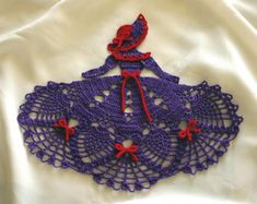 """All dressed up in purple and red, our pretty crochet crinoline girl doily boasts a full pineapple skirt and matching broad brimmed hat. Trimmed in plenty of bows, she's sure to be a favorite for the """"Red Hat Society"""" when worked in reds and purples. She's equally beautiful worked in other colors to compliment any decor"""