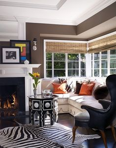 We love how the animal print rug adds a funky touch to this living room.  The rich brown walls are balanced with plenty of white trim.