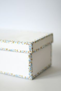 Take a shoe box, paint it the color you want and use some decorative take to outline the edges. You could actually use wallpaper, colorful duct take or craft paper...just all kinds of goodies. Love...love...love this idea.