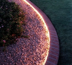 Great idea!  Rope lighting around the garden.  Inexpensive, waterproof and you can use a timer.