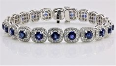 Stunning 18k white gold sapphire and diamond halo design tennis bracelet. Set with 22 round very fine blue sapphires, 7.15 tcw. Also set with 220 round brilliant diamonds weighing 4.25 tcw. Having F/G color and VS2 clarity.  Invisible clasp with hinge design.