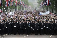 Police officers stand in front of royal supporters on The Mall in London, along the Processional Route by the Palace moments before William and Kate emerged to share a kiss