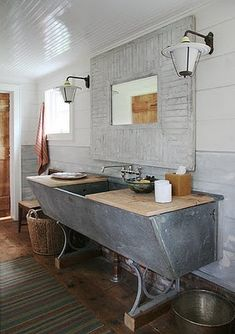 A giant farm sink, waincot ceiling and old light fixtures in the rustic bathroom.