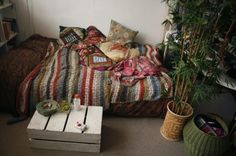 this will be my room. bed on floor for easy roll out. bamboo plant coverage and painted crate for a bedside table.
