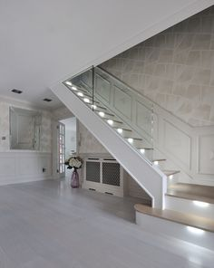 An ultra-modern staircase in light oak with LED lights installed under the treads to subtly illuminate the staircase.