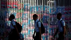 http://evememorial.org/index.html Students walk next to electoral posters plastered on a wall in a street of Port-au-Prince, Haiti, Sept. 26, 2016. | Foto: Reuters