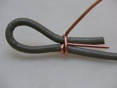 Loop ia piece of wire, and bend loop 90° to the stem of the wire (20g wire, 2mm leather). Then lay end of cord into wire loop, and fold tip of the cord back to make loop in cord. Keep the stem of the wire parallel to cord, and make sure that cord loop is sized for your project, since it is not adjustable! Then, wrap wire around cording (and stem of wire). Wrap DOWN cord, away from loop.