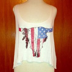 American flag cow skull tank crop top Graphic tee with an American flag cow skull and feathers on the left horn. Tank is a crop top and loose fitted. Has a deep neck and deep arm holes. Cute to wear with lace bralettes or colorful bandos/camis. White. 100% rayon. Made in the USA 1Mad Fit Tops Tank Tops