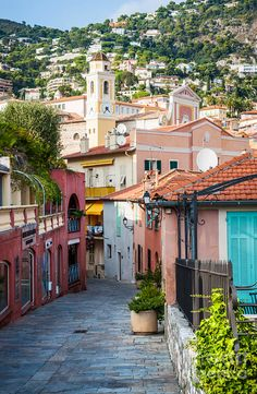 Cobblestone street with colourful buildings leads to the heart of old town and Eglise Saint-Michel in Villefranche sur Mer (Saint Michael's Church). By Elena Elisseeva.